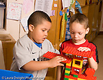 Preschool ages 3-5 two boys working together making structure out of connecting plastic Duplo bricks horizontal