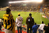 """Beitar Jerusalem soccer fans holding yellow and black flags support their team during the the match for the league against Bnei Sachnin in the Jerusalem stadium """"Tedy"""". Bnei Sachnin is the only Arab club in the Israeli Prime League, as a result of that the Betar chants are specially racist during the games between the clubs . Beitar Jerusalem FC was founded in the 1930's by the right-wing Revisionist Zionist movement, which later formed the Israeli Likud political party, during the British Mandate rule over Palestine. The chanting of the club is racist and mainly against Arabs. The team is the only one in the Israeli league to have never had an Arab player. Beitar is seen as the right wing and Mizrahi (Jews who came from Asia and Africa) club. Photo by Quique Kierszenbaum"""