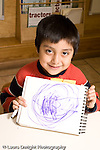 Education preschoool children ages 3-5 proud boy holding up his drawing meant to represent the circular earth vertical
