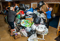 BNPS.co.uk (01202 558833)<br /> Pic: MaxWillcock/BNPS<br /> <br /> Pictured: Volunteers adding to the pile of donations.<br /> <br /> A flood of donations for Afghan refugees has inundated a church which has been left with a 24ft long stack of parcels.<br /> <br /> Ross Donaldson posted on a Facebook community group asking if anyone had clothes to offer, sparking an overwhelming response from his community.<br /> <br /> After organising to keep donations at Immanuel Church, Bournemouth, Dorset, he arrived the next morning to find a pile of bags.