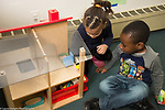 Education Preschool 3=4 year olds boy and  girl playing with dollhouse and small dolls