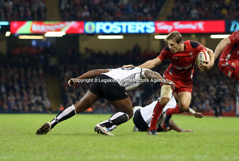 Pictured: Liam Williams of Wales (R) avoids a tackle by Vereniki Govena (L) of Fiji. Saturday 15 November 2014<br /> Re: Dove Men Series rugby, Wales v Fiji at the Millennium Stadium, Cardiff, south Wales, UK.