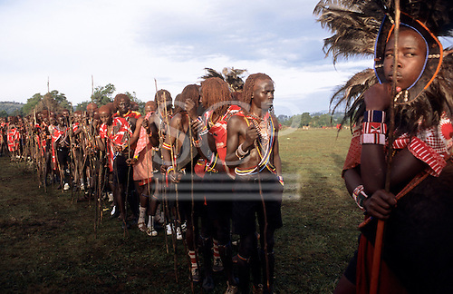 Lolgorian, Kenya. Line of Maasai moran warriors at Eunoto ceremony participating in the ceremony; Lion Head at front.