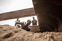 Men dig sand from a  cargo boat at a small port in Kibuye, Rwanda on Lake Kivu. Brendan Bannon. March 1, 2014