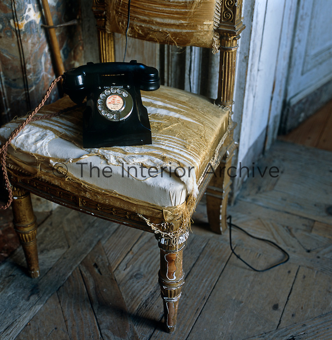An old-fashioned telephone on an antique chair with the remains of its silk upholstered seat