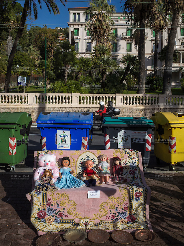 Italy. Liguria Region. Ospedaletti. Flea market on a sunny sunday morning. Dolls, a teddy bear, a carpet and brass plates for sell. On the road, four different recycling bins: waste (green), plastic( blue), bottles and aluminium cans (green), paper (yellow). A real estate sign for a home's sale and a couple riding a scooter. 3.01.16 © 2016 Didier Ruef