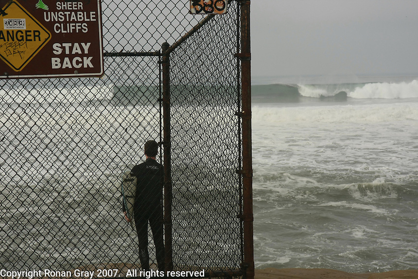 Surfer Jim O'Neill watches the surf from Sunset Cliffs in Ocean Beach, San Diego California just before entering the water on Wednesday, December 5 2007.  A large storm swell brought waves of more than 10ft to the area.
