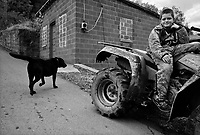 """War, WV, October 25 2008.William, 11, with his dog Bogger, on his """"fourwheeler"""", spends most afternoons roaming the surrounding hill trails.""""West Virginia Southernmost city"""", War is a small coal miners' town, hit hard by the economic crisis; many of its inhabitants will vote for Obama as McCain is perceived to be the man from the oil companies, trying to destroy the coal mining industry."""