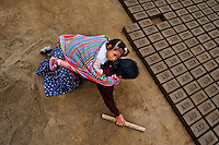 A Peruvian indigenous woman, carrying a baby on her back, works at a brick factory in Huachipa, a suburb in the outskirts of Lima, Peru, 10 August 2012. Child labour is a common practice at the artisanal brick factories, found predominantly in socially deprived areas of the urban zones. Poverty and lack of employment force parents, mainly season workers coming from rural areas of the country, to employ their own children, in an effort to ensure the livelihood for the whole family. Children aged 4-7 take part in simple jobs while children aged 8 and up tend to work regularly, same as adults. A family group, consisting of 2 adults and 2-3 children, may earn 20-25 USD per day, working almost the whole day, often in harsh climatic conditions.