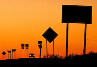Silhouette of highway objects at dusk, road signs, car with lit headlights, automobile, transportation; NR. Kansas, rural.