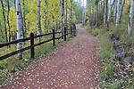 Red rock walking trail framed by split-rail fence and aspen, Telluride, Colorado, USA.