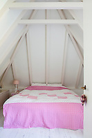 A waterbed nestles under the eves of the master bedroom, its pink chequered linen stands out against the white walls
