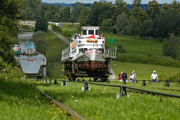 Boat on cable car being pulled uphill. Ostroda - Elblag Canal: Overland transportation of boats on rail cars at the Elblag Canal (Polish: Kanal Elblaskie, German: Oberlaendischer Kanal), Masuria, Poland, Europe. No releases available. ---Info: A system of rail-mounted cable trolleys on skipways and traditional locks are connecting the various sections of the Elblag Canal. A 100 metre difference in water levels is overcome during a length of 80 km between Ostroda and Elblag. The rail lift devices are mechanically driven by water power.--- HISTORY: The canal was designed in 1825-1844 by Georg Steenke, carrying out the commission given by the king of Prussia. Construction began in 1844. As the route was not important enough to justify building expensive, traditional locks between lakes, an ingenious system of tracks was employed instead, though the canal includes a few locks as well. Built originally under the name Oberländischer Kanal (Overland Canal) and situated in the Kingdom of Prussia, it was opened in 1860. Since 1945 the canal has been located in Poland. After wartime damage was repaired, it was restored to operation in 1948. Today it is used mainly for recreational purposes. It is considered one of the most significant monuments related to the history of technology on the territory of modern Poland..