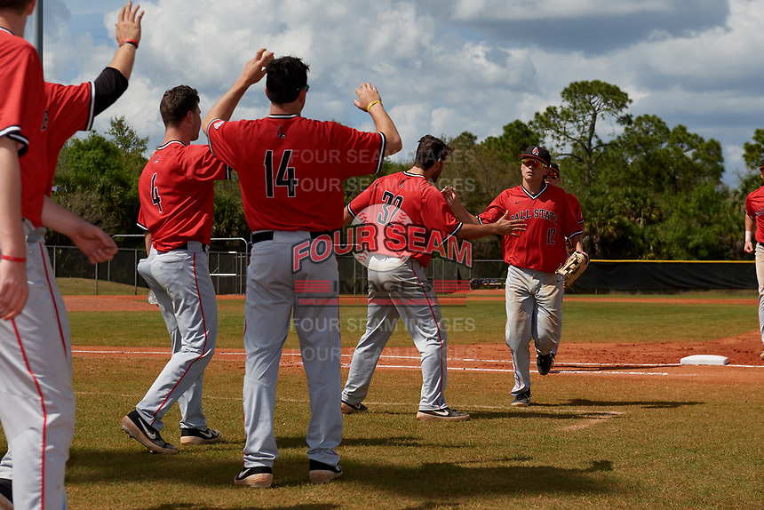 Ball State Cardinals left fielder Mack Murphy (12) high fives teammates William Baker (32), Langston Ginder (4), and Chandler Hughes (14) during a game against the Mount St. Mary's Mountaineers on March 9, 2019 at North Charlotte Regional Park in Port Charlotte, Florida.  Ball State defeated Mount St. Mary's 12-9.  (Mike Janes/Four Seam Images)