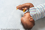 5 month old baby boy seen from above rolling as he grasps toy closup