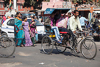 Jaipur, Rajasthan, India.  Mid-day Street Traffic in Central Jaipur.  Pedestrians, Rickshaws, and Cars all Share the Road.