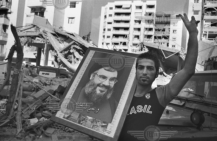 A supporter of Hezbollah (Hizbollah) holds a portrait of its leader Hassan Nasrallah next to the rubble of apartment buildings in Haret Hreik in the southern suburbs of Beirut. The area was bombed by the Israeli military during 34 days of conflict between Israel and Hezbollah.