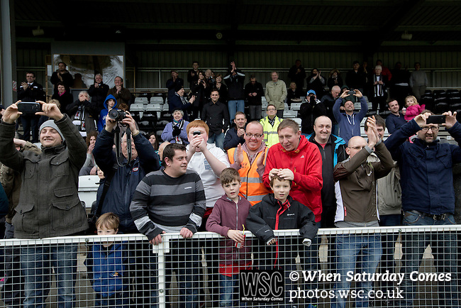 Cefn Druids AFC 1 Buckley Town 0, 12/04/2014. The Rock, Cymru Alliance league. Fans watching the home team captain Gareth Edwards lifting the league trophy at The Rock, Rhosymedre, home to Cefn Druids AFC, after the club's final home game of the season against Buckley Town (in yellow) in the Cymru Alliance league. Druids, reputedly the oldest football club in Wales, won the Alliance league the previous week and were awarded the trophy after the Buckley Town match, which they won by 1 goal to nil, watched by a crowd of 246. The Cymru Alliance was the second tier of Welsh football based in north and mid Wales, promotion from which led directly into the Welsh Premier League. Photo by Colin McPherson.