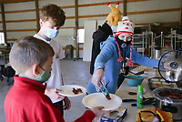 "Volunteer Tracy Hillis (right) serves food to Ben Kearbey, 11, (from left) and Will Kearbey, 15, of Springdale, Sunday, November 15, 2020 at Central United Methodist Church in Rogers. The Church hosted their Breakfast of Champions free breakfast distribution, which is part of their 11th annual Turkey Bowl. Central United Methodist and First United held a student-led competition to raise food for the Grace food pantry. The event also included a bowling night. Last year, they collected 3,200 items for the Grace food pantry. ""Grace in November and December sees a huge increase in need,"" said Lucy Swanson, director of youth ministries. ""The purpose is to help Grace survive November and December."" Check out nwaonline.com/201116Daily/ for today's photo gallery. <br /> (NWA Democrat-Gazette/Charlie Kaijo)"