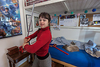 Switzerland. Canton Ticino. Pregassona. Elisabetta Montobbio stands in her bedroom and hold a sword in her hands. A cat is sleeping on the lower bunk bed. Star Wars poster on the wall. Elisabetta Montobbio is a dancing member of MOPS_DanceSyndrome which is an independent Swiss artistic, cultural and social organisation operating in the field of contemporary dance and disability. It is composed only of Down dancers. Down syndrome (DS or DNS), also known as trisomy 21, is a genetic disorder caused by the presence of all or part of a third copy of chromosome 21 It is usually associated with physical growth delays, mild to moderate intellectual disability, and characteristic facial features. A sword is a bladed melee weapon intended for slashing or thrusting that is longer than a knife or dagger, consisting of a long blade attached to a hilt. Pregassona is a quarter of the city of Lugano. 1.02.2020 © 2020 Didier Ruef