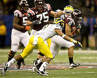 Josh Oglesby of Virginia Tech runs the ball away from Michigan defenders during Sugar Bowl game at Mercedes-Benz SuperDome in New Orleans, Louisiana on January 3rd, 2012.  Michigan defeated Virginia Tech, 23-20 in first overtime.
