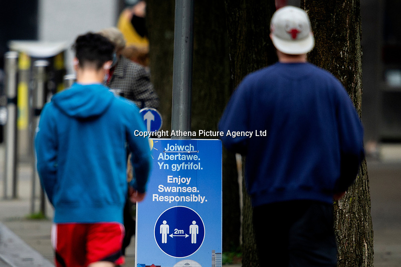 Pictured: Two young men walk past a keep your distance sign in St Mary's Square, Swansea city centre, Wales, UK. Monday 28 September 2020<br /> Re: Local lockdown will be in force from 6pm on the 27th September 2020 due to the Covid-19 Coronavirus pandemic, in Swansea, Wales, UK.