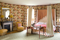 The walls of this four-poster bedroom are covered in a dramatic floral fabric