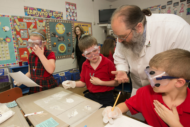 Jim Gay, a student teacher, explains polymers to Benjamin during his school's science day. Benjamin attends St. Francis de Sales Catholic School.
