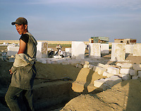 A mausoleum builder pauses at the end of the day at a coastal cemetery.