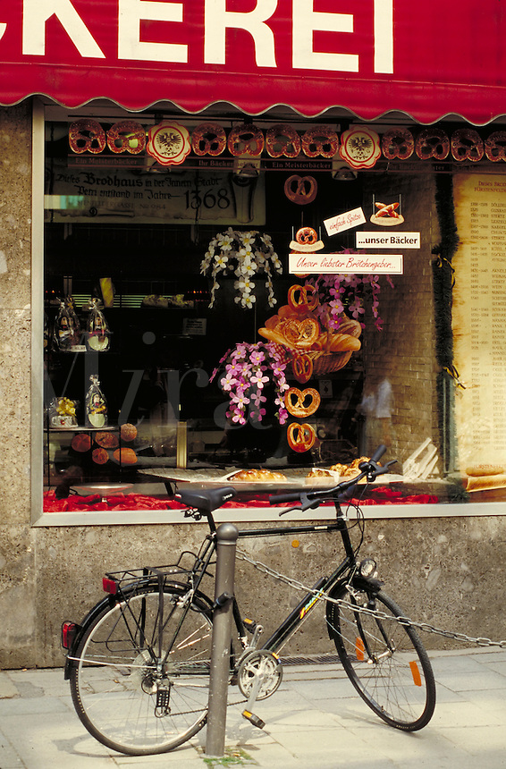 Bakery on Furstenfelderstrasse; baked goods, gifts and signs in window; bicycle parked by metal fencepost. Munich Bavaria Germany.