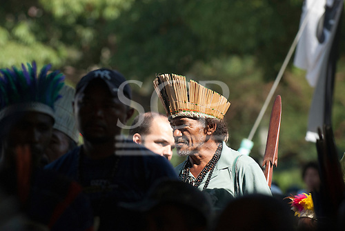 A Brazilian indigenous man wearing a reed headdress, beads of natural seeds and carrying a wooden war club moves through a crowd of indigenous people from various ethnic groups. The People's Summit at the United Nations Conference on Sustainable Development (Rio+20), Rio de Janeiro, Brazil, 18th June 2012. Photo © Sue Cunningham.