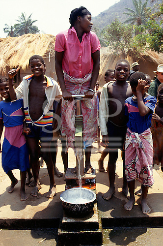 Kisamba Bay, Tanzania. Smiling children and girl in pink shirt using a village pump.