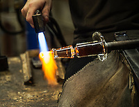 Glass artisan uses a hand torch to soften the piece he is working on.