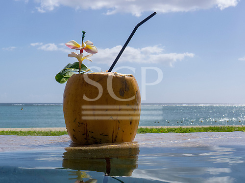 Flic en Flac, Mauritius. La Pirogue tourist resort. Coconut cocktail in the infinity pool by the beach.