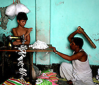 The owner of a textile factory beating a child labourer. The boy works for ten hours a day and earns $10.