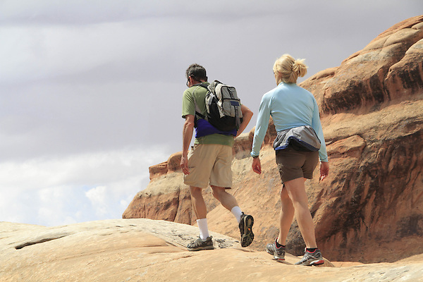 Man and woman walking on slickrock sandstone in Arches National PArk, Utah, USA. .  John offers private photo tours in Arches National Park and throughout Utah and Colorado. Year-round.