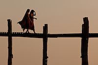 Monks crossing U Bein bridge at sunset, Mandalay, Myanmar