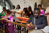 Switzerland. Canton Valais. St-Maurice. Africa Saints Pilgrimage (Pèlerinage aux Saints d'Afrique). Religious <br /> ceremony in St-Maurice's abbey. African women and men pray and light candles before a catholic mass. 2.06.13 © 2013 Didier Ruef