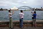 SYDNEY NSW, AUSTRALIA. 05 January 2010.  Japanese tourists take photographs of the Sydney Opera House and Harbour Bridge from the Botanical Gardens. As Australia's largest city , Sydney has some of the most beautiful beaches in the world to compliment the incredible Harbour the city is based around.
