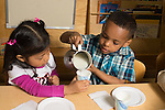 Preschool meal time boy pouring milk for friend