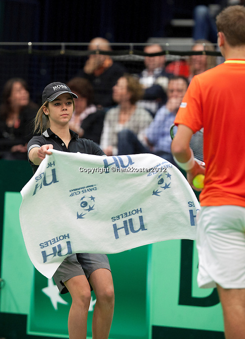10-02-12, Netherlands,Tennis, Den Bosch, Daviscup Netherlands-Finland, Ballenmeisje geeft een handdoek aan Thiemo de Bakker
