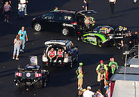 Sept. 14, 2012; Concord, NC, USA: NHRA funny car drivers Alexis DeJoria (top) and Courtney Force pull back into their pits during qualifying for the O'Reilly Auto Parts Nationals at zMax Dragway. Mandatory Credit: Mark J. Rebilas-