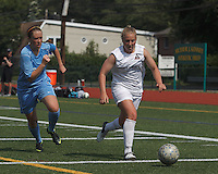 Boston Aztec forward Corey Persson (17) dribbles down the wing as Seacoast United Mariners midfielder Annie Koensgen (24) closes. In a Women's Premier Soccer League (WPSL) match, Boston Aztec (white) defeated Seacoast United Mariners (blue), 2-1, at North Reading High School Stadium on Arthur J. Kenney Athletic Field on on June 23, 2013. Due to injuries through the season, Seacoast United Mariners could only field 10 players.