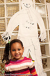 Preschool Headstart 3-5 year olds portrait of girl with lifesize drawing of person behind her vertical