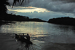 Family in dugout canoe returns home at dusk on the  Belize-Guatemalan border