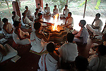 """Students at Om Shantidhama performing """"Yangan"""" - a way of worshiping the fire god. They perform it everday early in the morning. Om Shantidhama is a residential vedic school for boys. Nestled among the confluence of hills, forest and rivers - Om Shanti Dhama is a world removed from the maddeningly fast and often chaotic urban India. Students from allover the country are selected to take part in its Vedic and free education system. What is unique about this institute is that they have blended the traditional and modern education system. Here computer and science is taught with the same passion as the Vedas and Shastras, helping the students to grow spiritually as well as earn a living. Bonding with the nature and animal world is a mandatory part of the institute's curriculum. Karnataka, India. Arindam Mukherjee"""