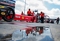 Jul 18, 2020; Clermont, Indiana, USA; The dragster of NHRA top fuel driver Leah Pruett and crew members reflect in a puddle as they prepare to fire up during qualifying for the Summernationals at Lucas Oil Raceway. Mandatory Credit: Mark J. Rebilas-USA TODAY Sports