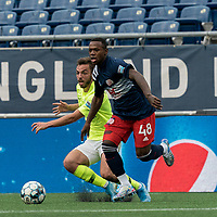 FOXBOROUGH, MA - MAY 12: Michel #48 of New England Revolution II dribbles as Damia Viader #3 of Union Omaha defends during a game between Union Omaha and New England Revolution II at Gillette Stadium on May 12, 2021 in Foxborough, Massachusetts.