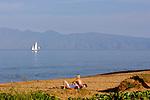 A young couple enjoy the sun on Kaanapali beach on the island of Maui.