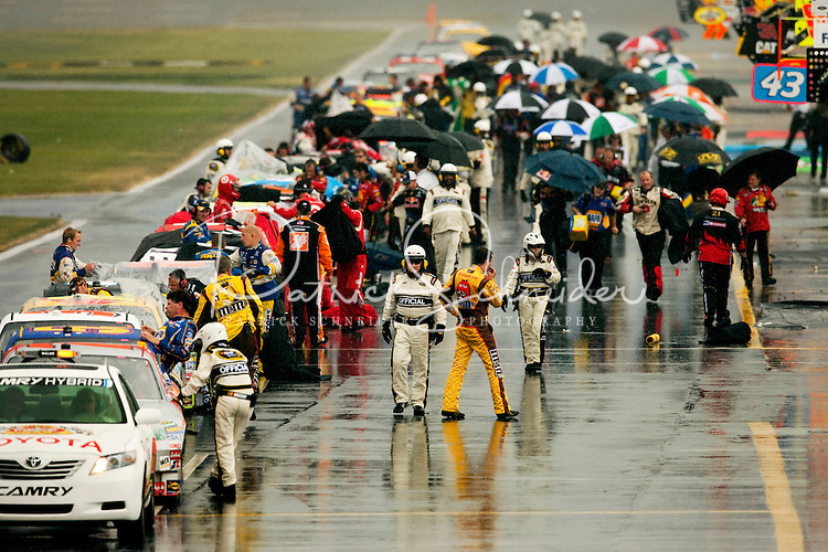 Race car drivers stop to wait out the rain along pit row at the Lowe's Motor Speedway, in Concord, NC, during the 2009 Coca-Cola Classic 600 NASCAR race. Driver David Reutimann won his first Cup race during the rain-shortened event, held May 25, 2009. NASCAR's longest scheduled race went only 227 laps, or 340.5 miles, before officials ended it because of rain. The 2009 race was the 50th running of the Coca-Cola 600. Ryan Newman and Robby Gordon finished second and third respectively.